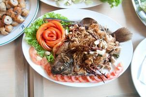 comida tailandesa peixe frito com acompanhamento de ervas