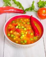 sopa de minestrone em uma tigela vermelha em fundo branco de madeira foto