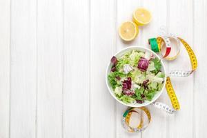 salada saudável fresca, utensílios e fita métrica sobre branco de madeira foto
