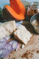 cozinhar ingredientes, legumes e queijo na mesa de corte foto