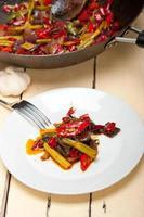 pimenta frita e legumes em uma panela wok foto