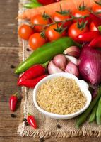 bulgur orgânico cru na tigela e legumes foto
