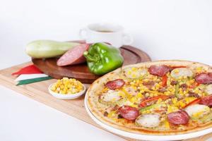 pizza italiana com abóbora, abobrinha, milho, pimentão, salsicha, salame foto