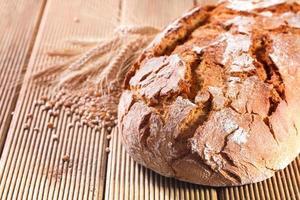 pão fresco com trigo no fundo de madeira foto
