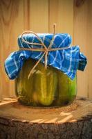 jar pepinos em conserva toco de madeira foto