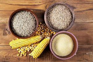 tigelas de milho, trigo, centeio, farinhas e cerâmicas na mesa de madeira