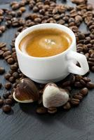 xícara de café expresso, fundo de grãos de café e bombons de chocolate foto