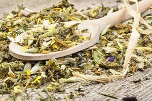 chá de ervas natural curativo na colher de pau na mesa velha foto