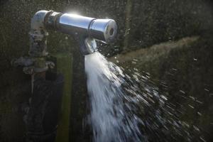 água da torneira na luz solar foto