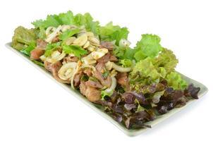 salada picante com carne de porco e ervas verdes em estilo tailandês foto