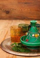 tagine e chá marroquino com hortelã em uma bandeja de metal foto