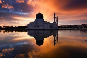 reflexão da mesquita da cidade de kota kinabalu ao nascer do sol