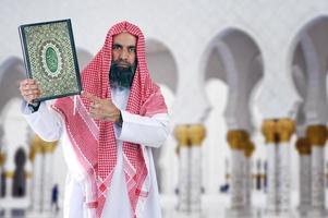 shiekh árabe islâmico apresentando Alcorão foto