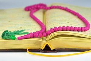 Alcorão com rosário orando contas em cores e páginas douradas foto