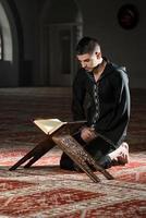 homem muçulmano em dishdasha está lendo o Alcorão