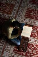homem muçulmano está lendo o Alcorão foto
