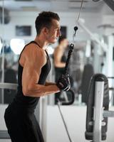 homem exercitar no treinador para os músculos tríceps foto