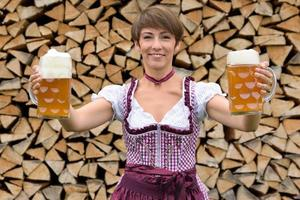 feliz mulher bávara segurando duas canecas de cerveja