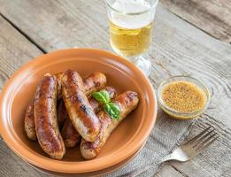 salsichas grelhadas com copo de cerveja foto