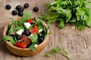 salada grega em uma tigela de salada de madeira em cima da mesa foto