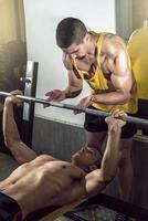 homem fazendo levantamento de peso com personal trainer foto