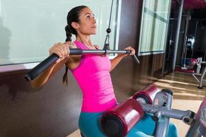 treino de mulher de máquina pulldown lat no ginásio foto