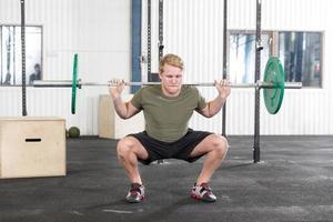 agachamentos treinando no centro de fitness ginásio foto