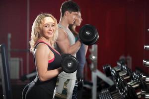 grupo de pessoas treinando com pesos livres no centro de fitness foto