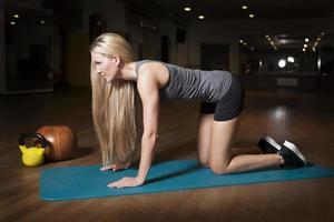 atleta feminina exercitando na esteira da ioga foto