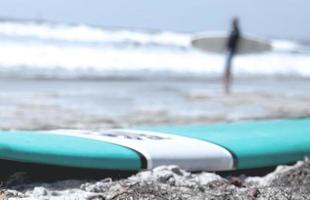 prancha azul na costa da praia de areia foto