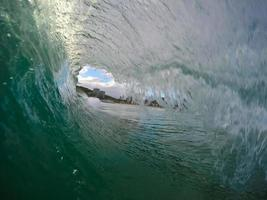 onda vítrea verde quebrando na praia foto