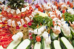 diferentes tipos de canapés na mesa de sobremesas para banquetes foto
