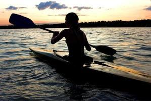 silhueta de kayaker feminino no meio de um lago foto