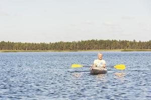 homem está dirigindo caiaque na água