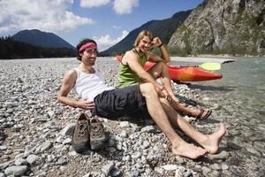 alemanha, baviera, tölzer terra homens com caiaque sentado na margem do rio foto
