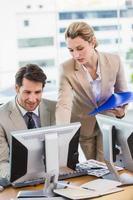 mulher mostrando seu colega algo na tela foto