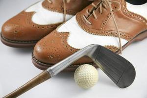 sapatos de golfe com o clube antigo foto