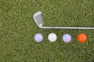 bola de golfe e clube de golfe na grama foto