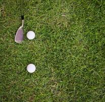 bola de golfe e ferro na grama foto