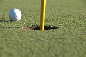 bola de golfe no verde perto do buraco foto
