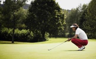 jogador de golfe examinando verde antes de colocar. foto