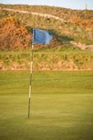 bandeira azul do campo de golfe, voando no vento foto