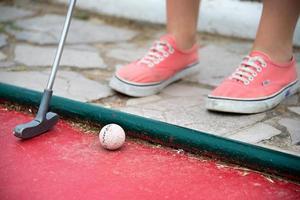 garoto jogando mini-golfe foto