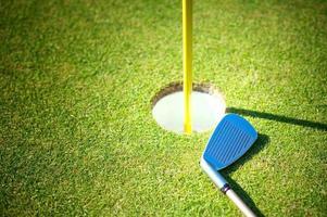 Taça de golfe com clube sobre fundo verde foto