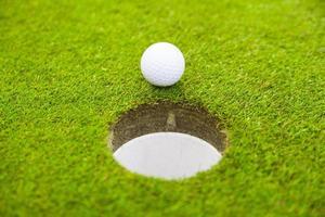 bola de golfe no lábio da taça. foto