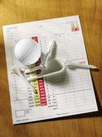 cartão de pontuação de golfe em uma mesa de madeira foto