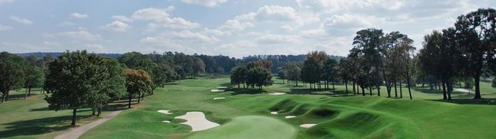 vista panorâmica de uma paisagem ensolarada com um campo de golfe foto
