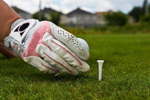 mão enluvada, colocando a bola de golfe no tee foto
