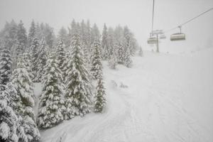 teleférico em queda de neve na estância de esqui alpino foto