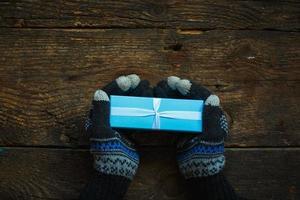 mãos em luvas de inverno com caixa de presente de natal foto
